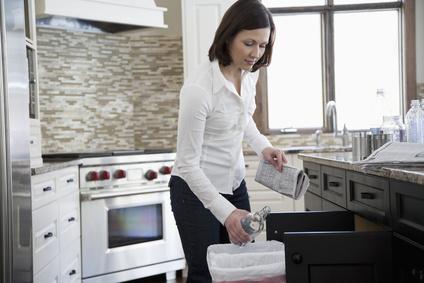 Einbaumülleimer Küche Frau wirft Flasche in Mülleimer