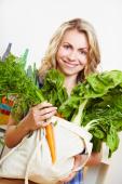 Frau mit Beutel voll losem Gemüse